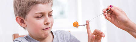 a little dinner: Little boy refuses to eat a dinner Stock Photo