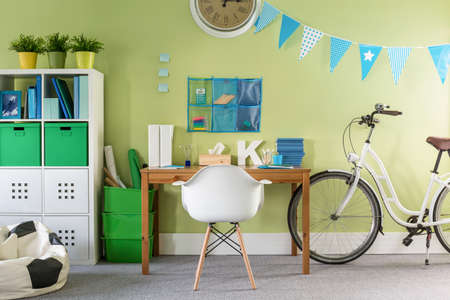 Photo of stylish bike standing in modern teenager room Stock Photo