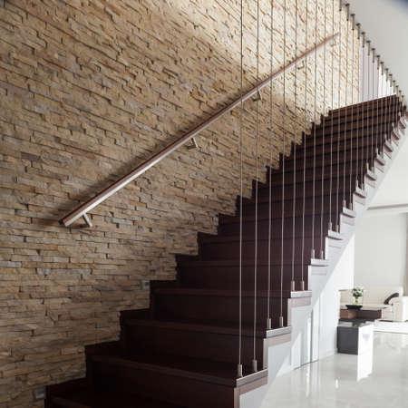 Pared de ladrillo y escaleras de madera en el interior diseñado