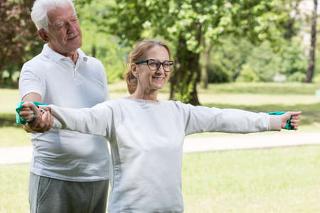 Image of athletic mature pair exercising together in the park
