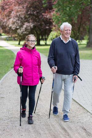 Foto de la pareja de ancianos haciendo nordic walking en el parque
