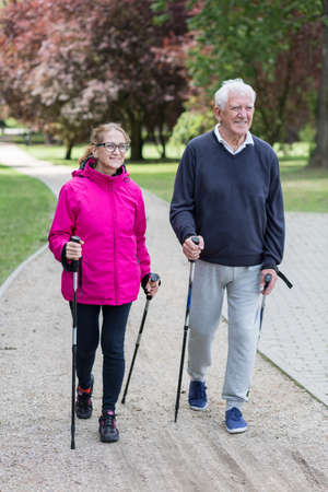 Photo of elderly couple doing nordic walking in the park