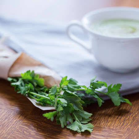 Parsley and white cup with creamy broccoli soup