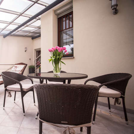 Designed wicker furniture on the cozy balcony Stock Photo