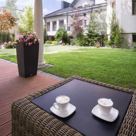 muebles de madera: Imagen de un patio de la casa con mesa de mimbre con estilo