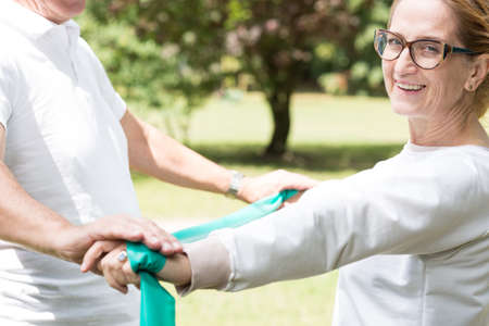 doing: Photo of elder sporty female doing sport in the park Stock Photo