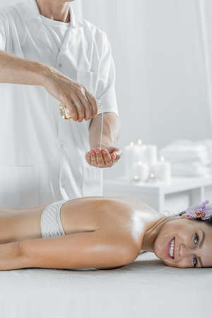 Picture of masseur doing healing olive oil body massage Stock Photo