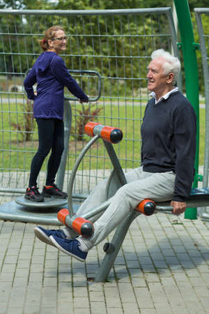 leisure activities: Image of elder people spending leisure time in outdoor gym Stock Photo