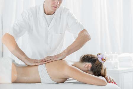 Photo of professional male masseur massaging womans back