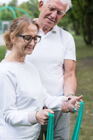 Picture of elder fitness woman holding elastic pilates band