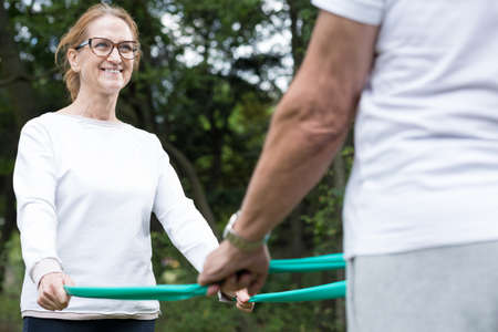 elastic band: Image of senior wife and husband during outdoor workout