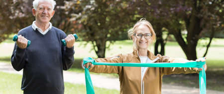Panorama of senior sporty pair exercising on fitness trail Stock Photo
