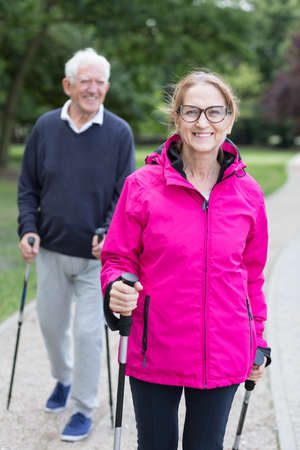 Image of sportive senior man and woman hiking in park