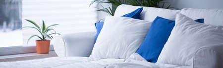 きちんとした白と青の寝具で快適なベッドのパノラマ 写真素材