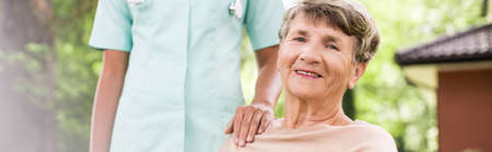 Panorama of happy elderly woman having private medical care