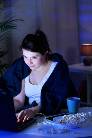junks: Girl is staying late and eating junk food Stock Photo