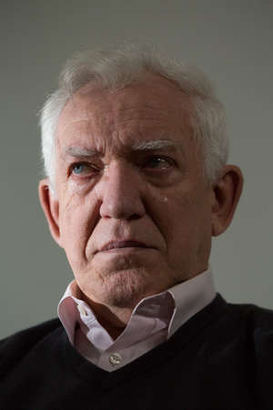 teardrop: Depressed senior man with teardrop on the check Stock Photo