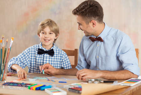 Picture of happy talented pupil drawing together with his teacher