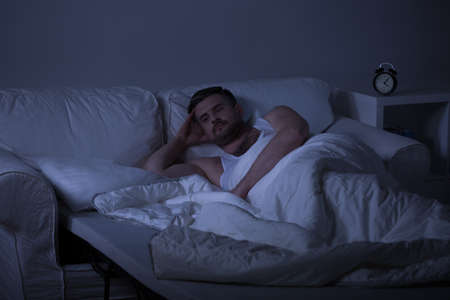 awake: Horizontal picture of man in bed thinking about his life