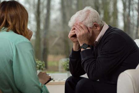 confide: Image of despair elder man during psychological therapy