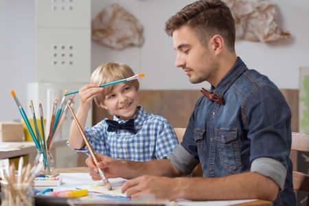 talented: Image of talented happy schoolboy with his paint teacher Stock Photo