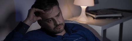 job loss: Photo of sad man sitting at night after job loss