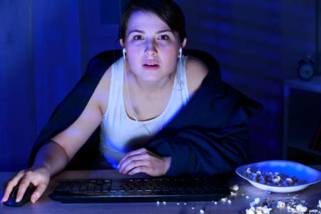 junk food: Young woman in front of the computers screen Stock Photo