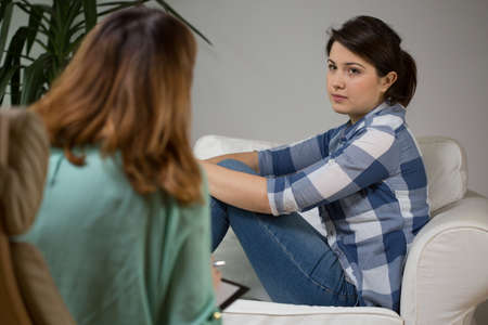 sessão: Jovem mulher sentada no sofá durante a terapia psicológica