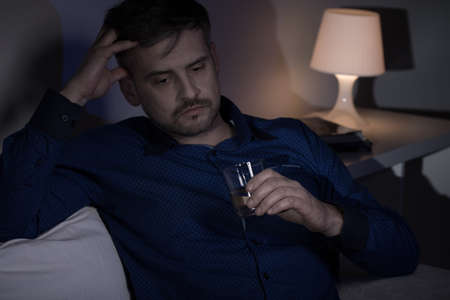 miserable: Photo of a miserable man drinking alcohol at night