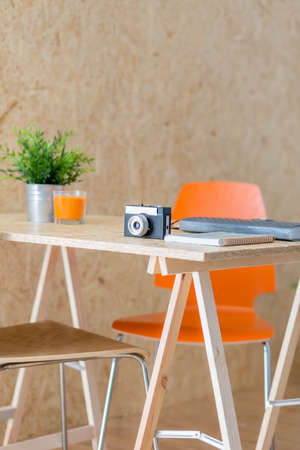 Image of camera lying on modern wooden table in studio