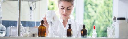 laboratorio: Farmacéutico de sexo femenino joven que trabaja en el laboratorio de química