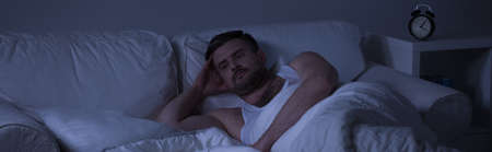stressing: Sad man unable to sleep because of memories from past