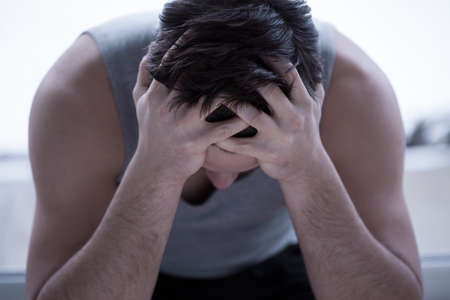 holding on head: Close up of depressed man holding head in his hands
