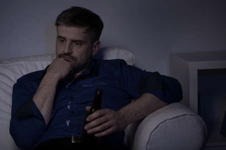 melancholijny: Horizontal picture of a melancholic man holdig bottle of beer