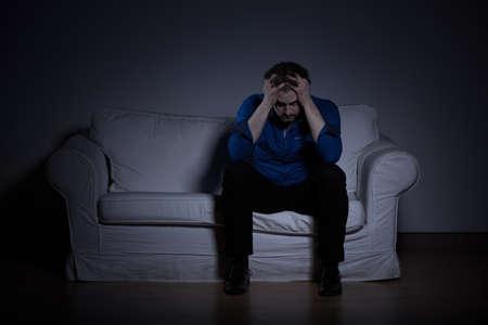 mentally: Photo of mentally broken man sitting on coach at night