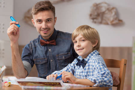 babysitter: Image of male babysitter with boy drawing a picture