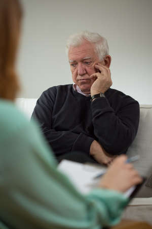 confide: Sad elder man talking with female psychiatrist