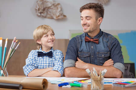 young male: Picture of smiling artistic preschooler during private painting lesson