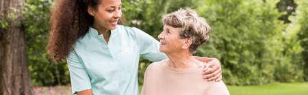 an elderly person: Panorama de la joven cuidador afroamericana femenina apoyo anciana Foto de archivo