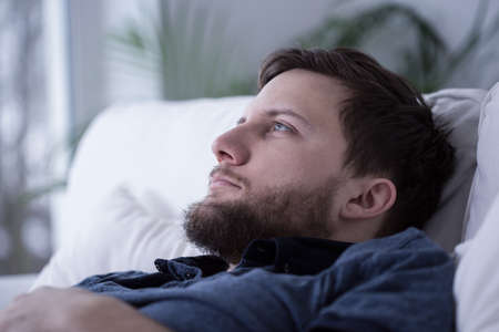 sleep disorder: Portrait of pensive tired male unable to fall asleep