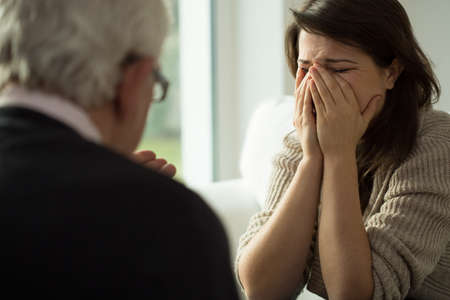 anxiety: Young depressed woman crying during psychological therapy