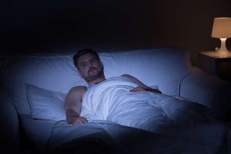 unhappy man: View of man at night suffering from insomnia