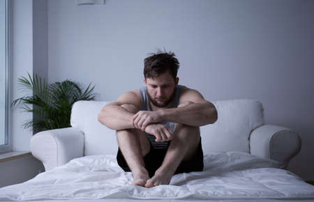 man sit: Image of man after mental breakdown sitting in bed