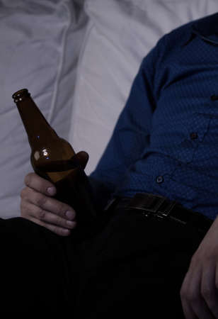 Close-up on a male hand holding bottle of beer