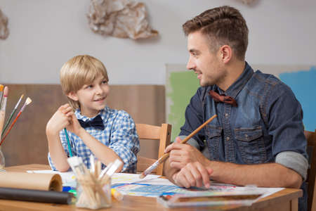 sibling: Picture of elder brother painting with his creative sibling