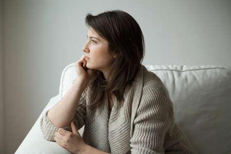 niña pensando: Muchacha triste que se sienta en el sofá y el pensamiento Foto de archivo