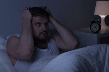 mentally ill: Horizontal view of mentally ill man at night in bed Stock Photo