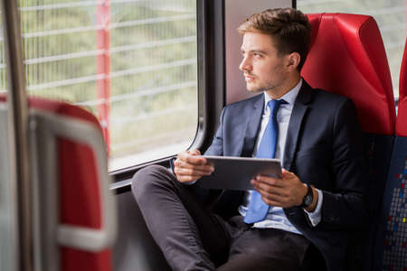 commuters: Image of male commuter in suit traveling by train