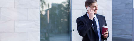 llamando: Hombre de negocios maduro llamando y tomando caf� al aire libre