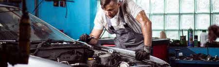 自動車修理工場で車のエンジンを修正 写真素材